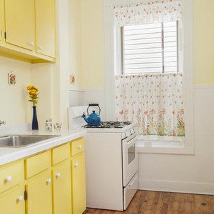 ニューヨークの小さいミッドセンチュリースタイルのおしゃれなキッチン (ドロップインシンク、フラットパネル扉のキャビネット、黄色いキャビネット、タイルカウンター、黄色いキッチンパネル、磁器タイルのキッチンパネル、白い調理設備、淡色無垢フローリング、アイランドなし) の写真
