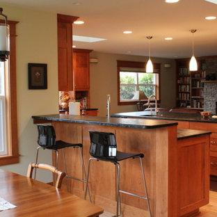 ポートランドの中サイズのエクレクティックスタイルのおしゃれなキッチン (ダブルシンク、シェーカースタイル扉のキャビネット、中間色木目調キャビネット、ソープストーンカウンター、マルチカラーのキッチンパネル、モザイクタイルのキッチンパネル、シルバーの調理設備、無垢フローリング) の写真