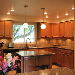Mid-sized traditional enclosed kitchen pictures - Example of a mid-sized classic l-shaped porcelain floor enclosed kitchen design in Seattle with a double-bowl sink, raised-panel cabinets, medium tone wood cabinets, beige backsplash, porcelain backsplash, stainless steel appliances and an island