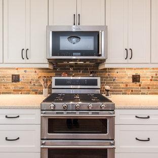 ワシントンD.C.の中くらいのトランジショナルスタイルのおしゃれなキッチン (アンダーカウンターシンク、シェーカースタイル扉のキャビネット、白いキャビネット、クオーツストーンカウンター、グレーのキッチンパネル、石タイルのキッチンパネル、シルバーの調理設備、クッションフロア、茶色い床、ベージュのキッチンカウンター) の写真