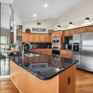 Mid-sized country u-shaped open plan kitchen in Orlando with an undermount sink, recessed-panel cabinets, medium wood cabinets, granite benchtops, black splashback, stainless steel appliances, medium hardwood floors, no island, brown floor and black benchtop.