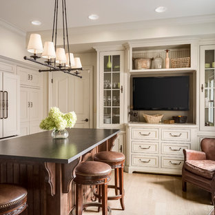 Inspiration for a traditional kitchen in Kansas City with a farmhouse sink, beaded inset cabinets, beige cabinets, granite benchtops, glass tile splashback, panelled appliances, light hardwood floors and with island.