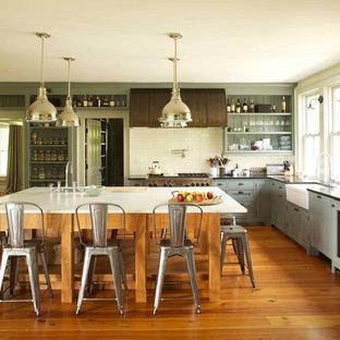 ボストンのヴィクトリアン調のおしゃれなキッチン (エプロンフロントシンク、シェーカースタイル扉のキャビネット、グレーのキャビネット、ソープストーンカウンター、白いキッチンパネル、磁器タイルのキッチンパネル、パネルと同色の調理設備、無垢フローリング) の写真
