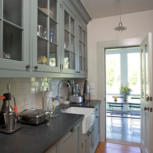 This is an example of a country galley kitchen in New York with a farmhouse sink, glass-front cabinets, grey cabinets, soapstone benchtops, white splashback, porcelain splashback and medium hardwood floors.