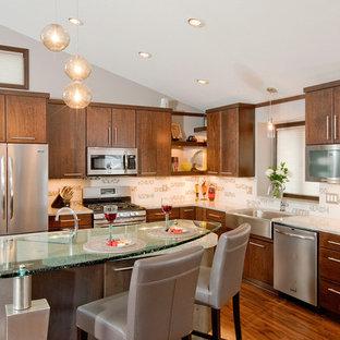ミネアポリスのコンテンポラリースタイルのおしゃれなキッチン (ガラスカウンター、フラットパネル扉のキャビネット、中間色木目調キャビネット、シルバーの調理設備の、エプロンフロントシンク、マルチカラーのキッチンパネル、セラミックタイルのキッチンパネル、無垢フローリング、茶色い床) の写真