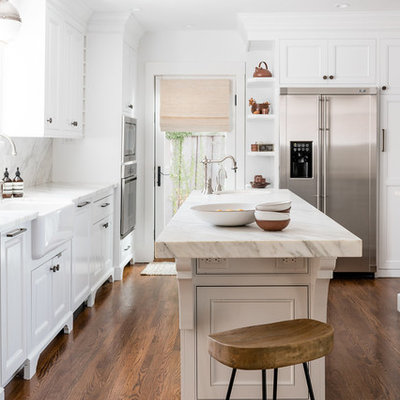 Transitional u-shaped medium tone wood floor and brown floor kitchen photo in Sacramento with a farmhouse sink, white cabinets, stainless steel appliances, an island and white countertops