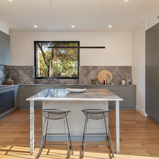 Design ideas for a mid-sized contemporary l-shaped kitchen in Melbourne with flat-panel cabinets, grey cabinets, grey splashback, stone slab splashback, light hardwood floors, with island and grey benchtop.