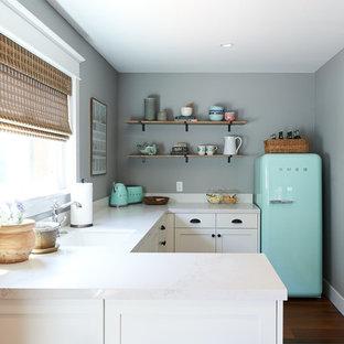 Inspiration för avskilda, mellanstora maritima u-kök, med en undermonterad diskho, skåp i shakerstil, vita skåp, bänkskiva i kvarts, vitt stänkskydd, en köksö, brunt golv, färgglada vitvaror och mörkt trägolv