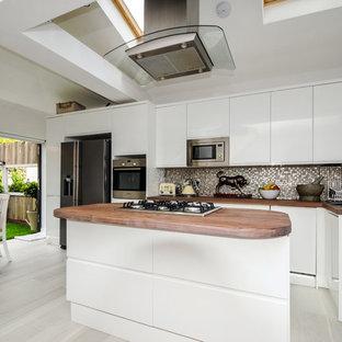 Diseño de cocina lineal, actual, de tamaño medio, abierta, con puertas de armario de madera clara, encimera de zinc, salpicadero metalizado, salpicadero con mosaicos de azulejos, suelo de baldosas de porcelana y una isla