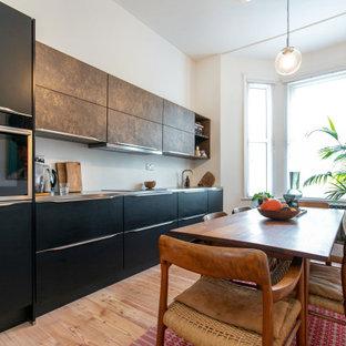 Bild på ett mellanstort funkis grå linjärt grått kök och matrum, med en integrerad diskho, luckor med upphöjd panel, svarta skåp, bänkskiva i rostfritt stål, vitt stänkskydd, stänkskydd i tegel, svarta vitvaror, ljust trägolv och beiget golv