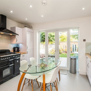 Inspiration for a medium sized contemporary galley kitchen/diner in Hertfordshire with shaker cabinets, white cabinets, wood worktops, no island, brown worktops, a built-in sink, multi-coloured splashback, glass tiled splashback, integrated appliances, porcelain flooring and grey floors.