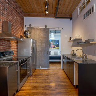 Design ideas for an industrial galley kitchen in Boston with a double-bowl sink, flat-panel cabinets, black cabinets, brick splashback, stainless steel appliances, medium hardwood floors, no island and black benchtop.