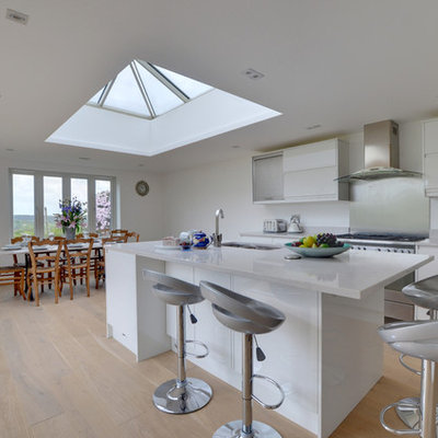 Large minimalist single-wall light wood floor and beige floor eat-in kitchen photo in Kent with an undermount sink, flat-panel cabinets, white cabinets, metallic backsplash, metal backsplash, stainless steel appliances, an island and white countertops
