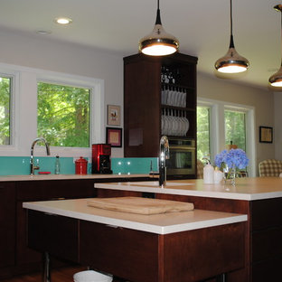 This is an example of a mid-sized midcentury l-shaped kitchen in Atlanta with a single-bowl sink, flat-panel cabinets, dark wood cabinets, glass benchtops, glass sheet splashback, stainless steel appliances, light hardwood floors and with island.