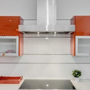 ワシントンD.C.の大きいコンテンポラリースタイルのおしゃれなキッチン (フラットパネル扉のキャビネット、オレンジのキャビネット、人工大理石カウンター、白いキッチンパネル、ガラス板のキッチンパネル、シルバーの調理設備の、コンクリートの床) の写真