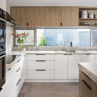 Photo of a large eclectic l-shaped open plan kitchen in Perth with white cabinets, solid surface benchtops, grey splashback, stone tile splashback, black appliances, ceramic floors, with island, grey floor and multi-coloured benchtop.