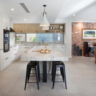 パースの大きいエクレクティックスタイルのおしゃれなキッチン (白いキャビネット、人工大理石カウンター、グレーのキッチンパネル、石タイルのキッチンパネル、黒い調理設備、セラミックタイルの床、グレーの床、マルチカラーのキッチンカウンター) の写真