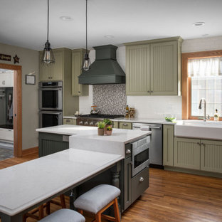 This is an example of a large traditional l-shaped eat-in kitchen in Columbus with a farmhouse sink, recessed-panel cabinets, green cabinets, quartz benchtops, white splashback, ceramic splashback, stainless steel appliances, medium hardwood floors, multiple islands, brown floor and white benchtop.