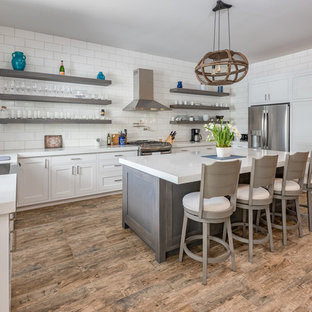 Farmhouse kitchen appliance - Inspiration for a farmhouse u-shaped brown floor kitchen remodel in San Francisco with shaker cabinets, quartz countertops, a farmhouse sink, white cabinets, white backsplash, subway tile backsplash, stainless steel appliances, an island and white countertops