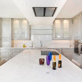 Cette image montre une petit cuisine ouverte design en L avec un évier 3 bacs, un placard avec porte à panneau encastré, des portes de placard beiges, un plan de travail en marbre, une crédence blanche, une crédence en marbre, un électroménager en acier inoxydable, un sol en carrelage de porcelaine, un îlot central, un sol beige et un plan de travail blanc.