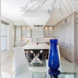 Inredning av ett modernt litet vit vitt kök, med en trippel diskho, luckor med infälld panel, beige skåp, marmorbänkskiva, vitt stänkskydd, stänkskydd i marmor, rostfria vitvaror, klinkergolv i porslin, en köksö och beiget golv