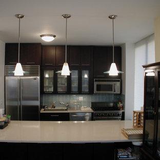 ニューヨークの小さいコンテンポラリースタイルのおしゃれなキッチン (アンダーカウンターシンク、フラットパネル扉のキャビネット、濃色木目調キャビネット、クオーツストーンカウンター、青いキッチンパネル、セラミックタイルのキッチンパネル、シルバーの調理設備の、トラバーチンの床) の写真