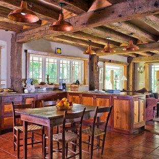 Immagine di una grande cucina stile rurale con lavello sottopiano, ante con bugna sagomata, ante in legno scuro, top in granito, paraspruzzi marrone, paraspruzzi in lastra di pietra, elettrodomestici in acciaio inossidabile, penisola, pavimento in terracotta e pavimento rosso