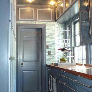 Diseño de cocina de galera, moderna, pequeña, cerrada, con fregadero encastrado, puertas de armario grises, encimera de madera, salpicadero azul, salpicadero de azulejos de vidrio, suelo de baldosas de terracota y suelo marrón