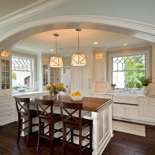 Cette image montre une cuisine traditionnelle avec un placard à porte vitrée, un évier de ferme et un plan de travail en bois.