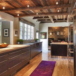 Immagine di una grande cucina ad U stile rurale con elettrodomestici in acciaio inossidabile, lavello integrato, ante lisce, ante in legno scuro, top in cemento, pavimento in travertino e 2 o più isole