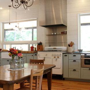 Modelo de cocina comedor en L, de estilo de casa de campo, de tamaño medio, sin isla, con electrodomésticos blancos, puertas de armario azules, armarios estilo shaker, encimera de esteatita, salpicadero blanco, fregadero sobremueble y suelo de madera en tonos medios