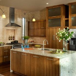 Mittelgroße Klassische Wohnküche in L-Form mit Küchengeräten aus Edelstahl, Unterbauwaschbecken, flächenbündigen Schrankfronten, hellbraunen Holzschränken, Arbeitsplatte aus Recyclingglas, Küchenrückwand in Beige, Rückwand aus Mosaikfliesen, dunklem Holzboden, Kücheninsel und braunem Boden in Atlanta