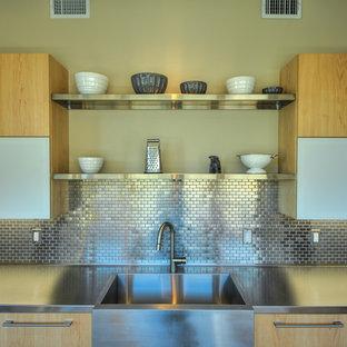 Idéer för att renovera ett funkis kök, med en rustik diskho, släta luckor, skåp i ljust trä, bänkskiva i rostfritt stål och stänkskydd med metallisk yta