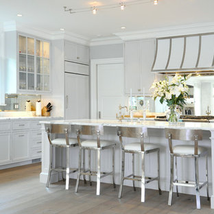 Traditional kitchen ideas - Elegant l-shaped kitchen photo in New York with shaker cabinets, gray cabinets, metallic backsplash, mirror backsplash and paneled appliances