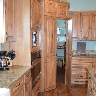 Lantlig inredning av ett kök, med en rustik diskho, luckor med upphöjd panel, skåp i ljust trä, bänkskiva i kvartsit, rostfria vitvaror, vinylgolv och en köksö