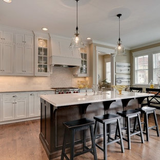 Traditional eat-in kitchen designs - Example of a classic eat-in kitchen design in Minneapolis with stainless steel appliances and stone tile backsplash