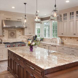 Foto de cocina tradicional con armarios con paneles con relieve, puertas de armario beige, salpicadero beige, electrodomésticos de acero inoxidable y salpicadero de piedra caliza