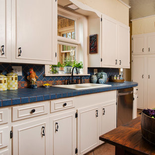 ダラスのトラディショナルスタイルのおしゃれなキッチン (タイルカウンター、ドロップインシンク、青いキッチンパネル、白いキャビネット、青いキッチンカウンター) の写真