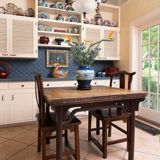 Photo of a traditional eat-in kitchen in Dallas with louvered cabinets, beige cabinets and blue splashback.