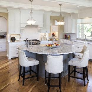 Modelo de cocina clásica con fregadero bajoencimera, armarios estilo shaker, puertas de armario blancas, encimera de mármol, salpicadero blanco, salpicadero de azulejos tipo metro, electrodomésticos de acero inoxidable, suelo de madera en tonos medios y una isla