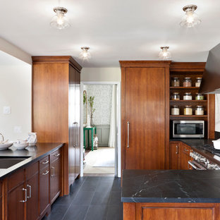 Photo of a mid-sized transitional kitchen in DC Metro with a peninsula, flat-panel cabinets, medium wood cabinets, soapstone benchtops, white splashback, porcelain splashback, stainless steel appliances, an undermount sink, porcelain floors and black benchtop.