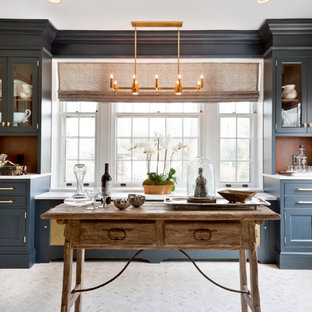 Small traditional galley kitchen in DC Metro with blue cabinets, marble benchtops, panelled appliances and marble floors.