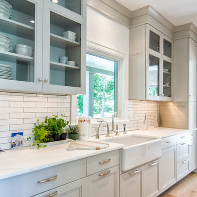Eat-in kitchen - mid-sized country single-wall light wood floor eat-in kitchen idea in New York with an undermount sink, shaker cabinets, white cabinets, granite countertops, white backsplash, subway tile backsplash, stainless steel appliances and an island
