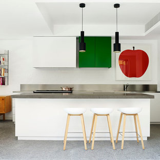 Mid-sized contemporary eat-in kitchen appliance - Example of a mid-sized trendy galley eat-in kitchen design in Sydney with flat-panel cabinets, white cabinets, an island and stainless steel countertops