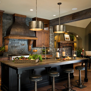 Inspiration for a country galley eat-in kitchen in New York with raised-panel cabinets, dark wood cabinets, black splashback, stainless steel appliances, dark hardwood floors, with island and slate splashback.
