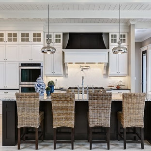 Photo of a large traditional l-shaped open plan kitchen in Boise with shaker cabinets, white cabinets, white splashback, subway tile splashback, stainless steel appliances, an island, light hardwood floors, a farmhouse sink and granite benchtops.