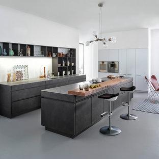 Imagen de cocina de galera, minimalista, de tamaño medio, abierta, con fregadero bajoencimera, armarios con paneles lisos, puertas de armario grises, encimera de cemento, salpicadero blanco, electrodomésticos de acero inoxidable, suelo de cemento y una isla