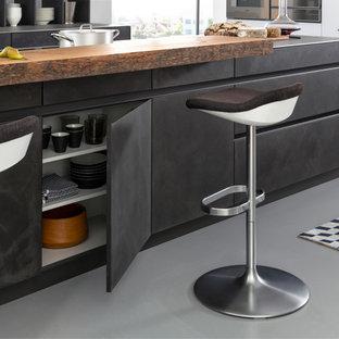 Offene, Zweizeilige, Mittelgroße Moderne Küche mit Unterbauwaschbecken, flächenbündigen Schrankfronten, grauen Schränken, Betonarbeitsplatte, Küchenrückwand in Weiß, Küchengeräten aus Edelstahl, Betonboden und Kücheninsel in New York