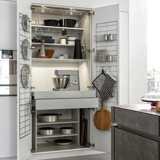 Idee per una cucina ad ambiente unico moderna di medie dimensioni con lavello sottopiano, ante lisce, ante grigie, top in cemento, paraspruzzi bianco, elettrodomestici in acciaio inossidabile, pavimento in cemento e isola