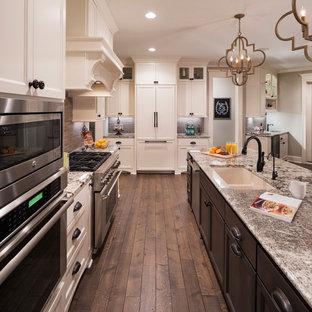 На фото: большая п-образная кухня-гостиная в классическом стиле с островом, врезной раковиной, фасадами с утопленной филенкой, белыми фасадами, темным паркетным полом, столешницей из гранита, коричневым фартуком, техникой из нержавеющей стали и коричневым полом с